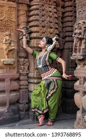 Gorgeous Odissi dancer striking pose against the backdrop of Mukteshvara Temple with sculptures in bhubaneswar, Odisha, India