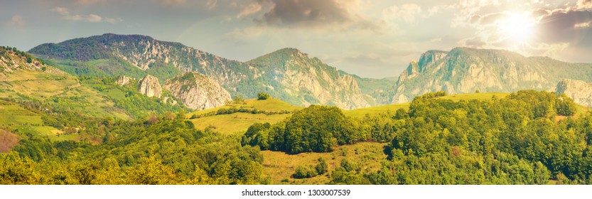gorgeous panorama of countryside at sunset in evening light. beautiful landscape of romania. rural area on the near hills. distant ridge with rocks, cliffs and gorge. wonderful sunny afternoon
