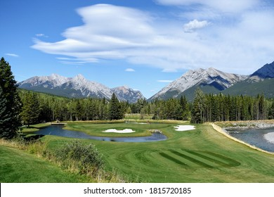 Gorgeous par 3 on a golf course surrounded by forest and big mountains in the background, on a beautiful sunny day in Kananaskis, Alberta, Canada. - Shutterstock ID 1815720185