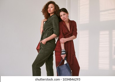 Gorgeous portrait of elegant couple of black and asian women in fashionable green and red suits isolated on white background