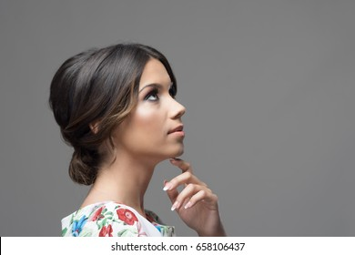 Gorgeous profile of latin hispanic beauty woman with finger under chin thinking and looking up at copyspace over gray studio background.