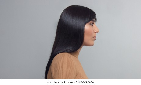 gorgeous profile of young brunette mixed race eastern woman with ideal shiny straight hair