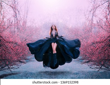 gorgeous red-haired hot woman in long flying black dress fluttering, witch turns into crow, dark queen in frozen spring flowering forest, levitation and flight, open breasts and bare sexy legs