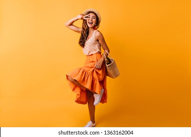 Gorgeous red-haired white woman dancing in studio. Dreamy girl in long skirt having fun on orange background.
