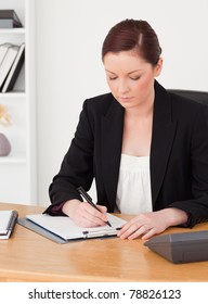 Gorgeous red-haired woman in suit writing on a notepad while sitting in an office