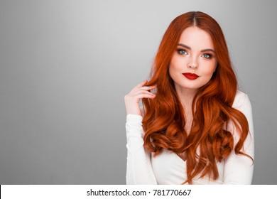 Gorgeous redhead girl with wavy hair beauty studio portrait