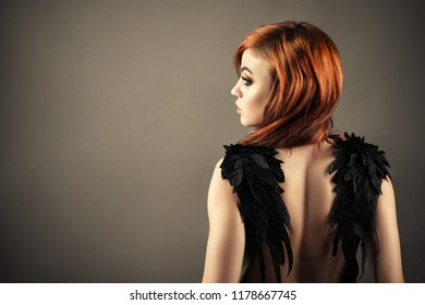 gorgeous redhead woman with black wings