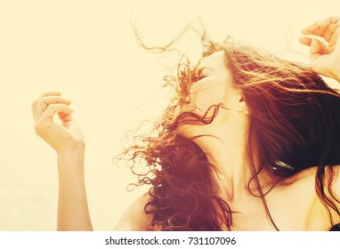Gorgeous Romantic Girl Outdoors. Long Hair Blowing in the Wind. Backlit, Warm Color Tones