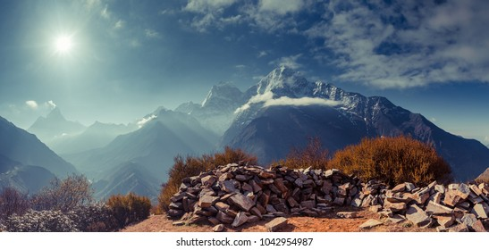 The gorgeous scene the boulders on the mighty misty snow-covered mountain background. The Himalayas. Everest Base Camp trek in the Sagarmatha National Park in the north-eastern Nepal.