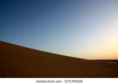 Gorgeous and scenic desert scene with the moon crescent high above beautiful sand dunes near Siwa Oasis in Egypt