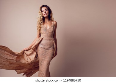 Gorgeous  seductive woman with blonde wavy hairs posing in studio. wearing elegant beige sequins  dress. Space for text. Beige background.