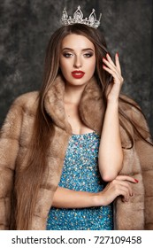 Gorgeous sensual woman with brunette long hair in luxurious mink fur coat and diamond crown fashion studio portrait. Fashionable jewelry model in ivory furs and evening blue dress isolated.