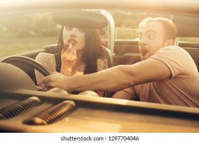 Gorgeous sexy copule of man and woman on a vacation car trip in summer day. Husband screams until his wife applying lipstick using the rear view mirror in the moving car. Distracted dangerous driving