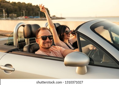 Gorgeous sexy copule of man and woman on a vacation car trip in summer day. Luxury grey sport car. Sexy fit brunette woman and man in casual outfit. Sunset