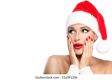 Gorgeous sexy young woman with bare shoulders in a red Santa hat with matching lipstick and manicured nails pouting her lips in a surprised expression, isolated on white with copy space for your text