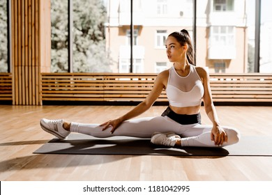 Gorgeous slim dark-haired girl dressed white sports top and tights is doing stretching on the mat for fitness in the gym