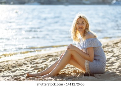 Gorgeous smile young blonde barefoot woman in blue dress sitting on the white sand of river beach at sunset