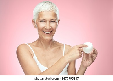 Gorgeous smiling Caucasian senior woman trying out new anti age cream and looking at camera. Beauty photography.