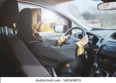 Gorgeous smiling muslim woman dressed in traditional wear driving her car.