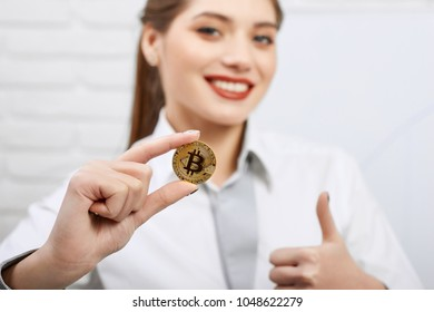 Gorgeous smiling woman holding golden bitcoin being main cryptocurrency and showing thumbs up as concept of successful innovative financial trend. Horizontal shot, blurred background.