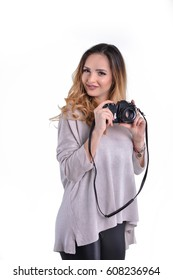 Gorgeous smiling woman holding a vintage film camera, wearing black latex pants and a west