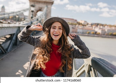 Gorgeous smiling woman with long curly hair posing with pleasure on bridge on blur background. Outdoor photo of blissful white lady enjoying autumn weekend in Europe.