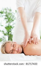 Gorgeous smiling woman relaxing on a lounger during massage with eyes closed in a wellness center