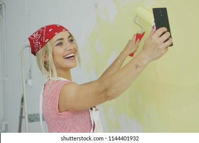 Gorgeous smiling young female in red bandana painting wall with roller and taking photo on smartphone front camera
