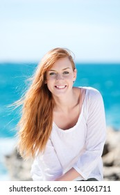 Gorgeous smiling young redhead woman with her back to the ocean looking at the camera