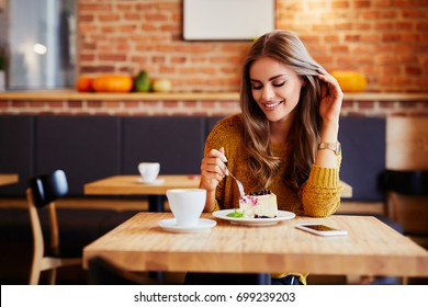 Gorgeous smiling young woman eating cake and drinking coffee at a cafeteria