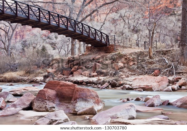 Gorgeous soft water shot of the Virgin River with a wooden bridge in Zion's National Park
