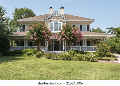 Gorgeous southern home with wrap around white porch and blooming crepe myrtle trees