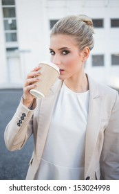 Gorgeous stylish businesswoman drinking coffee outside on urban background