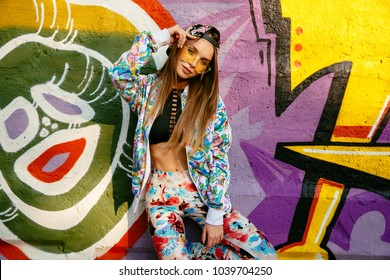 Gorgeous stylish girl in sunglasses, with long hair standing on background of wall with colorful graffiti. Dressed in fashionable suit, singlet and cap. Outdoors.