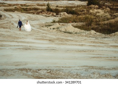 gorgeous stylish happy blonde bride and  elegant groom on a sand on a background of beautiful sunny lake at sunset