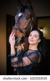 Gorgeous stylishly dressed woman in dark lace boho style dress and gold jewelry with a thoroughbred horse. The concept of love human and animals, horses and rider lifestyle