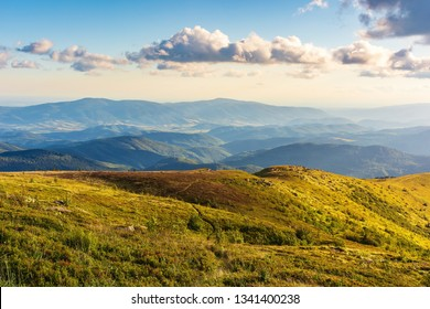 gorgeous summer mountain landscape at sunset. fluffy clouds on a blue sky above the hills in golden light. grassy alpine meadow on the slopes. ridge and valley in the distance