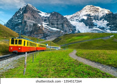 Gorgeous summer travel experience, popular electric red tourist train with high snowy Swiss mountains in background, near Kleine Scheidegg station, Bernese Oberland, Switzerland, Europe