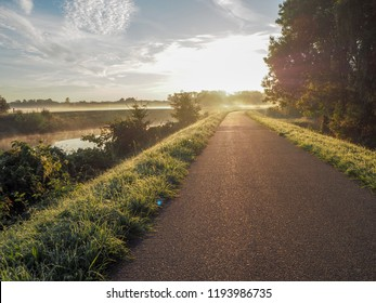 Gorgeous sunrise over the pathway next the river Dyle near Mechelen, Belgium, during an early misty morning in September