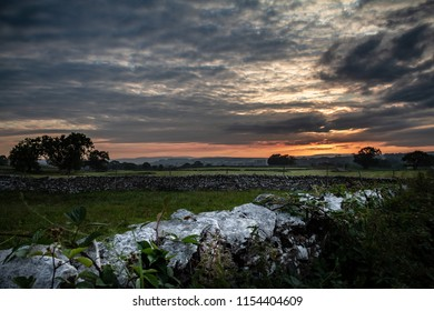 Gorgeous sunset over the fields and old dividing stones in the Lake District in Cumbria, England UK.