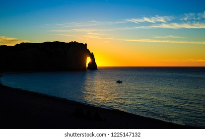 Gorgeous sunset over sea in Etretat, Normandy. Famous cliff is backlit with the last reys of the declining sun.