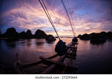 A gorgeous sunset silhouettes the bow of a ship as it lays at anchor in a remote lagoon surrounded by limestone islands in Raja Ampat, Indonesia.