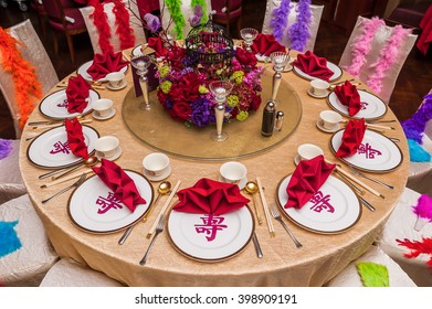 Gorgeous table layout at Chinese restaurant for celebration event with words meaning longevity on plates.