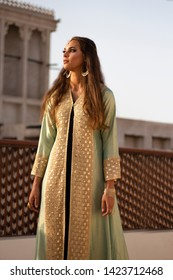 Gorgeous tall model looking like a princess in a majestic torquoise and golden Arabic kaftan robe. She is standing in the balcony of a traditional Arabic palace/fort. The dress is mirror worked.