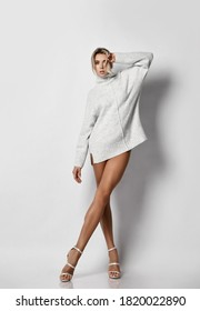 Gorgeous tall sexy blonde woman in knitted sweater and high-heeled shoes stands with her naked long legs crossed holding hand at head. Sexy female look and perfect body concept