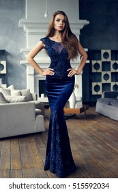Gorgeous tall slim glamorous woman in long blue lace luxury evening dress standing in lounge interior with wooden floor. Brunette beautiful stunning girl looking at you. Vogue style portrait