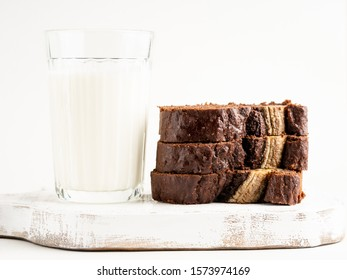 Gorgeous tasty chocolate banana cake (banana bread) sliced and decorated with banana split on white wooden cutting board with a glass of milk, white background