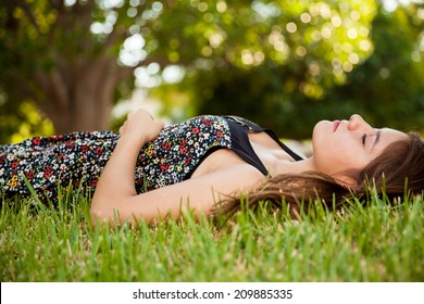 Gorgeous teen laying on the grass and taking a nap at a park