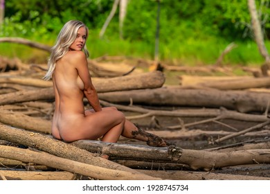 A gorgeous topless blonde model enjoys a summers day outdoors in a park