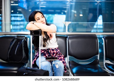 Gorgeous traveler girl sit on a chair at airport. Beautiful woman is waiting airline calling. The airline postpone for takeoff. It is delay flight. Charming beautiful girl feels boring. copy space